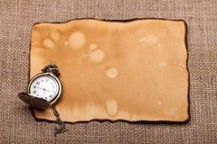 Kieszeniowy zegarek przy starym papierem Fotografia Stock