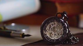 Kieszeniowy zegarek z starymi książkami i pióro z papierową mapą na stole okno zbiory wideo