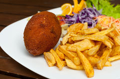 Kiev cutlet. Dish with french fries and vegetables on a wooden table background Royalty Free Stock Photo