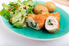 Kiev cutlet with jacket potatoes and salad stock image