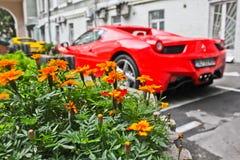 Kiev, de Oekraïne; 10 april, 2014 Bloemen op de achtergrond van supercar Ferrari 458 Italië De lente De zomer royalty-vrije stock afbeeldingen