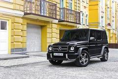 Kiev, de Oekraïne; 21 april, 2015 Mercedes-Benz G55 AMG tegen de achtergrond van het gele huis royalty-vrije stock fotografie