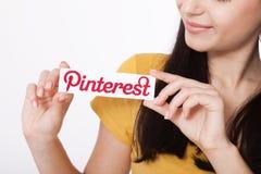 KIEV, DE OEKRAÏNE - AUGUSTUS 22, 2016: De vrouwenhanden die Pinterest houden ilogotype bedriegen gedrukt document Is foto delend  Stock Fotografie