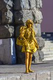 Kiev, de Oekraïne, 07 augustus 2018 Meisje die een standbeeld op een stadsstraat afschilderen Een het leven standbeeld in goud wo stock foto's