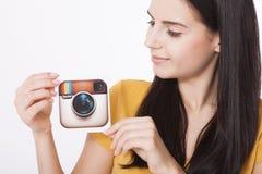 KIEV, DE OEKRAÏNE - AUGUSTUS 22, 2016: Vrouwenhanden die de camerapictogram gedrukt document houden van Instagram logotype Is onl Royalty-vrije Stock Afbeeldingen