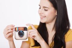 KIEV, DE OEKRAÏNE - AUGUSTUS 22, 2016: Vrouwenhanden die de camerapictogram gedrukt document houden van Instagram logotype Is onl Royalty-vrije Stock Afbeelding