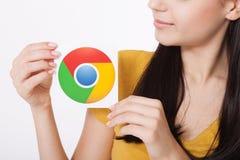 Kiev, de Oekraïne - Augustus 22, 2016: Vrouwenhanden die Google Chrome-pictogram houden die op papier op grijze achtergrond wordt Royalty-vrije Stock Afbeelding