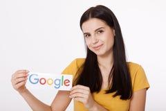 Kiev, de Oekraïne - Augustus 22, 2016: Vrouwenhanden die Google houden die logotype op papier op grijze achtergrond wordt gedrukt Stock Foto