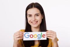 Kiev, de Oekraïne - Augustus 22, 2016: Vrouwenhanden die Google houden die logotype op papier op grijze achtergrond wordt gedrukt Royalty-vrije Stock Fotografie