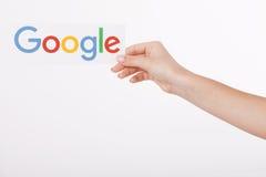 Kiev, de Oekraïne - Augustus 22, 2016: Vrouwenhanden die Google houden die logotype op papier op grijze achtergrond wordt gedrukt Royalty-vrije Stock Afbeelding
