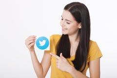 KIEV, DE OEKRAÏNE - AUGUSTUS 22, 2016: Vrouwenhanden die icoivogel gedrukt document houden van Twitter logotype Twitter is online Royalty-vrije Stock Afbeeldingen