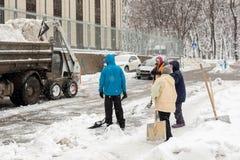 KIEV, DE OEKRAÏNE - 21 DECEMBER, 2017: De arbeiders maakt gang bij flatgebouwwerf tijdens schoon zware sneeuwval Stock Foto's