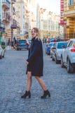 Kiev, de Oekraïne 30 03 2019 Het jonge meisje in zwarte kleren in de lente zonnige dag loopt op oude stadsstraten Kleding, jasje  royalty-vrije stock afbeelding