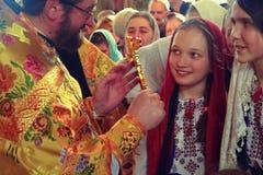 Kiev, de Oekraïne, 12 Maart, 2016 Kiev, de Oekraïne, 12 Maart 2016 jong meisje die en het kruis glimlachen bekijken Stock Fotografie