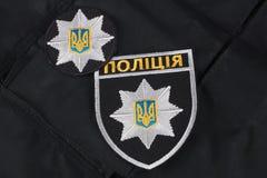KIEV, DE OEKRAÏNE - NOVEMBER 22, 2016 Flard en kenteken van de Nationale Politie van de Oekraïne op zwarte eenvormige achtergrond stock afbeelding