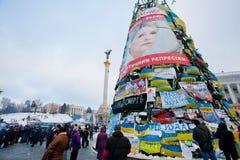 KIEV, DE OEKRAÏNE: Reusachtige Kerstmisboom met banners, vlaggen en affiches op de hoofdstraat bezet door demonstratiesystemen Stock Foto's