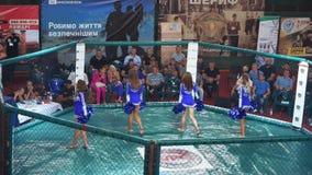 KIEV, de Oekraïne - September 22, 2018: Cheerleadersmeisjes in de blauwe kleding die met pom poms in achthoek dansen stock video