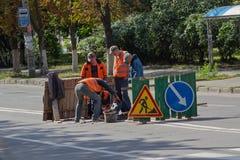 Kiev, de Oekraïne - September 10, 2015: De nutsarbeiders asfalteren op de weg Stock Foto