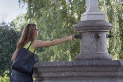 Kiev, de Oekraïne - September 09, 2015: De vrouw vraagt een muntstuk goed geluk aan de fontein-magneet aan Royalty-vrije Stock Afbeelding