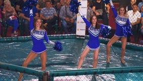 KIEV, de Oekraïne - September 22, 2018: Meisjescheerleaders in blauwe kleding die met pom poms in de ring dansen stock videobeelden