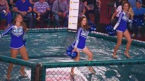 KIEV, de Oekraïne - September 22, 2018: Meisjescheerleaders in een blauw kleedt het dansen met pom poms in achthoek stock video