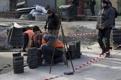 Kiev, de Oekraïne 10 01 2018 zette het Reparatiewerk, arbeiders een voetweg uit tegels stock foto's