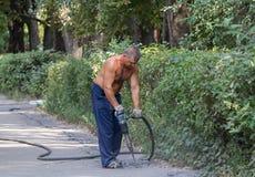 Kiev, de Oekraïne - September 01, 2015: Arbeider die een jackhammer gebruiken Stock Afbeeldingen