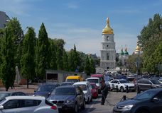 Old St. Sophia church, busy modern street. Kiev. The modern cars are slowing down and stacked in traffic jam. On the background the beautiful green square and Stock Images
