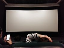Cinema white screen with seats and people silhouettes. Kiev, March 6, 2018, Ukraine. People are watching the screen in the cinema hall. Semi-empty cinema hall Royalty Free Stock Photography