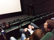 Cinema white screen with seats and people silhouettes. Kiev, March 6, 2018, Ukraine. People are watching the screen in the cinema hall. Semi-empty cinema hall Royalty Free Stock Image