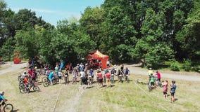 Kiev/Oekraïne-Juni, 1 Hommel die van 2019 rond beginlijn vliegen met fietsers die voor het ras van de bergfiets in groen park voo stock footage