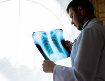 Kiev region, Ukraine - October 12.2016: Dr. therapist in an office looking x-ray the patient`s lungs Royalty Free Stock Photos
