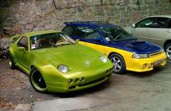 Kiev 2010 September 14; Porsche 928 rovfågel i frodig gräsplan och Subaru STI royaltyfri fotografi