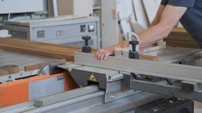 Kiev UA, 30-05-2019 Carpintero de sexo masculino que trabaja en la máquina circular en taller, trabajador que corta el tablón de  metrajes