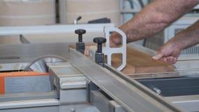 Kiev UA, 30-05-2019 Carpintero de sexo masculino que trabaja en la máquina circular en taller, trabajador que corta el tablón de  almacen de video