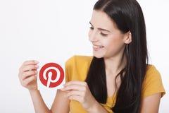 KIEV, UCRÂNIA - 22 DE AGOSTO DE 2016: Mãos da mulher que guardam o papel impresso ícone de Pinterest É a foto que compartilha do  Fotografia de Stock Royalty Free