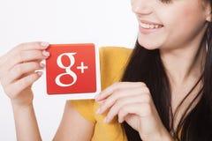 Kiev, Ucrânia - 22 de agosto de 2016: A mulher entrega guardar Google mais o ícone impresso no papel no fundo cinzento Google é E Imagens de Stock Royalty Free