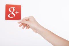 Kiev, Ucrânia - 22 de agosto de 2016: A mulher entrega guardar Google mais o ícone impresso no papel no fundo cinzento Google é E Foto de Stock Royalty Free