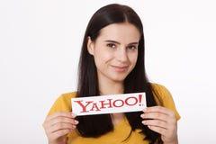 Kiev, Ucrânia - 22 de agosto de 2016: A mulher entrega guardar o logotipo dos ícones de Yahoo do tipo impressos no papel no cinza Foto de Stock Royalty Free