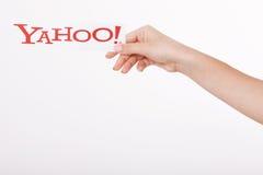 Kiev, Ucrânia - 22 de agosto de 2016: A mulher entrega guardar o logotipo dos ícones de Yahoo do tipo impressos no papel no cinza Imagem de Stock Royalty Free