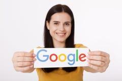 Kiev, Ucrânia - 22 de agosto de 2016: A mulher entrega manter o logotype de Google impresso no papel no fundo cinzento Google é E Imagens de Stock