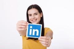 KIEV, UCRÂNIA - 22 de agosto de 2016: A mulher entrega manter o sinal do ícone de Linkedin impresso no papel no fundo branco Link Imagens de Stock Royalty Free