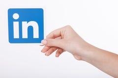 KIEV, UCRÂNIA - 22 de agosto de 2016: A mulher entrega manter o sinal do ícone de Linkedin impresso no papel no fundo branco Link Imagens de Stock