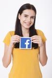 KIEV, UCRÂNIA - 22 de agosto de 2016: A mulher entrega manter o sinal do ícone do facebook impresso no papel no fundo branco Face Imagens de Stock Royalty Free