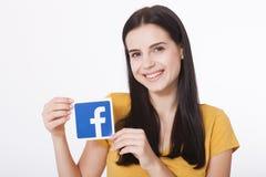 KIEV, UCRÂNIA - 22 de agosto de 2016: A mulher entrega manter o sinal do ícone do facebook impresso no papel no fundo branco Face Imagem de Stock