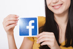KIEV, UCRÂNIA - 22 de agosto de 2016: A mulher entrega manter o sinal do ícone do facebook impresso no papel no fundo branco Face Fotografia de Stock Royalty Free