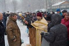 Kiev, Ucrânia - 18 de janeiro de 2018: O padre polvilha os paroquianos da igreja com água consagrado Foto de Stock Royalty Free