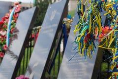 Kiev, Ucrânia - 2 de julho de 2017: Fitas nas cores da bandeira nacional amarrada por cidadãos no monumento Imagem de Stock