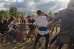 Kiev, Ucrânia - 6 de julho de 2017: Os indivíduos e as meninas puxam a corda na celebração do festival de Ivan Kupala Imagens de Stock