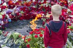 Kiev, Ucrânia - 9 de maio de 2016: Menino na chama eterno no memorial de soldados caídos Imagens de Stock